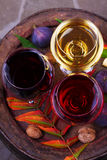 Red, rose and white glasses of wine. Grape, fig, nuts and leaves on old wooden barrel. View from above, top studio shot. Royalty Free Stock Photo