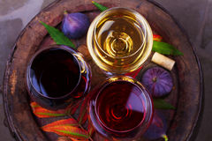 Red, rose and white glasses of wine. Grape, fig, nuts and leaves on old wooden barrel. View from above, top studio shot. Red, rose and white glasses of wine royalty free stock images