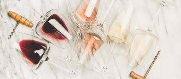Red, rose, white wine in glasses and corkscrews, horizontal composition. Flat-lay of red, rose and white wine in glasses and corkscrews over grey marble stock photos