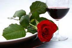 Red rose and wine. Dinner setting with red rose and red wine Royalty Free Stock Photography