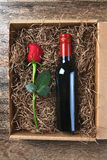 Red Rose Wine Bottle Box. A single red rose and a bottle of wine in a cardboard box filled with packing material. High angle shot. Valentines / Love / Romance Stock Photography