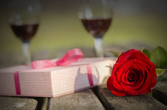 Red, rose, wineglass, gift, wooden table Stock Photos