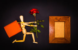 Red rose and wooden man on black background Stock Photos