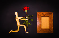 Red rose and wooden man on black background Royalty Free Stock Photos
