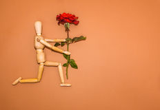 Red rose and wooden man on brown background Stock Photo