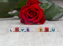 Red rose and the word love written on decorative cubes Stock Image