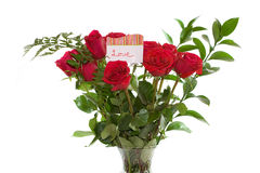 Red roses. A closeup horizontal picture of a bouquet of beautiful red roses with a card that says Love in them on an isolated white background Royalty Free Stock Image