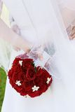 Red roses. A bride holding her flowers behind her back Stock Photography