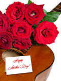 Red roses on acoustic guitar isolated for Mother's Day Stock Photo
