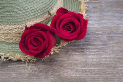 Red roses on a background weave hats. Stock Photo