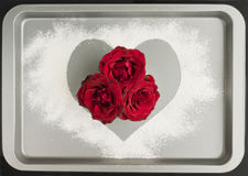 Red roses baking with love. Red roses in a heart shape made of flour on a new and shiny metal baking tray royalty free stock photo