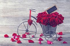 Red roses in bicycle vase. On a wooden background Royalty Free Stock Images