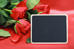 Red roses and blac board Royalty Free Stock Photography