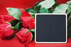 Red roses and black board for congratulations Royalty Free Stock Photography