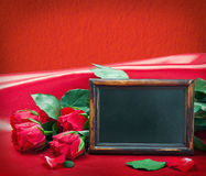 Red roses and blackboard with space for text. On a red background Stock Photos