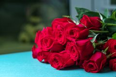 The red roses are on the blue surface the background is blurred stock photos