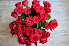 Red roses bouquet on grey background, top view Stock Images