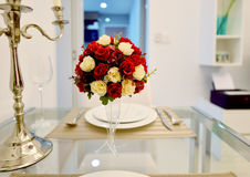 Red Roses Bouquet in the middle of dining table in modern living Stock Photography