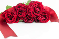 Red roses bouquet with ribbon on white table Stock Photo