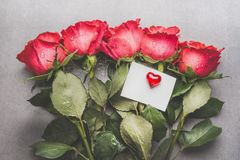 Red roses bunch with blank paper card and heart, top view. Mock up for greeting stock images