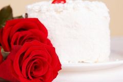 Red roses and a cake on the table Royalty Free Stock Image