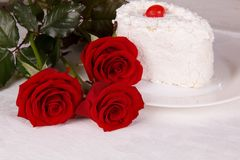 Red roses and a cake on the table Royalty Free Stock Photo