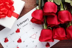 Red roses with calendar on february. Bouquet of red roses with calendar on february and gift box on wooden table stock image