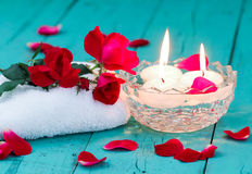 Red roses and candles on teal blue wood background Royalty Free Stock Photography