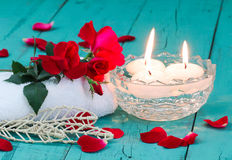 Red roses and candles on teal blue wood background Stock Image