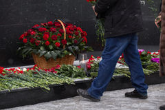 Red roses and carnation symbol of mourning - laying flowers to the monument Stock Image