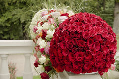 Red roses centerpiece flower ball. Red rose flower ball, a large outdoor festive centerpiece standing on the stairs on a white fence with colorful flowers and stock images