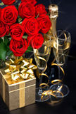 Red roses, champagne and golden gift. Festive decoration Stock Photo