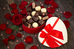 Red roses and chocolate pralines in red heart shaped gift box Stock Photo