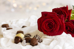 Red roses and chocolate. Valentine red roses and chocolate on white fabric with sparkling background Stock Image