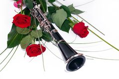 Red roses and clarinet. Three red roses and clarinet composition over white stock photos