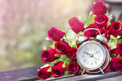 Red roses and clock on the background. And wood Royalty Free Stock Image