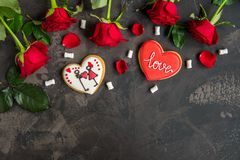 Red roses and cookie shaped heart with text Love, dark backgroun Stock Image