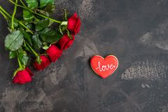 Red roses and cookie shaped heart with text Love, dark backgroun Stock Images