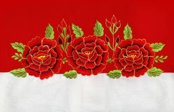 Red roses embroidery. Three red roses embroidery on red and white linen Royalty Free Stock Photo