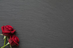Red roses on empty slate background. Red roses on slate background with space for text stock photos
