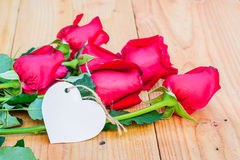 Red roses and empty tag. Royalty Free Stock Photos