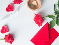 Red roses, envelope, heart shaped candles on the white backgroun. Valentine`s day flat lay: red roses, envelope, heart shaped candles on the white background Royalty Free Stock Images