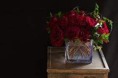 Red Roses Flower Arrangement With Black Background. Floral arrangement of red roses on a vase, on a wooden pedestal with a black background Royalty Free Stock Photography