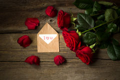 Red roses flower and petals  and envelope with text I love you.  Royalty Free Stock Image