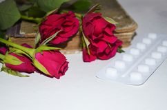 Tablets with roses flowers. Red roses flowers with film -coated tablets  on white Royalty Free Stock Images