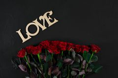 Red Roses Flowers With Wooden Word LOVE On Black Background With Royalty Free Stock Photo