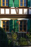 Red roses on framework facade with window green shutters. On a sunny summer morning in south germany city schwaebeisch gmuend stock photo