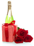 Red roses, gift and  bottle of champagne Stock Image