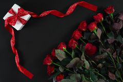 Red roses and gift box on black background. Top view. Flat lay. Copy space. Still life Valentine`s Day Stock Photography