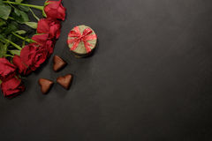 Red roses, gift box and chocolate hearts with copy space. On black Royalty Free Stock Image